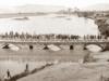 Η πανέμορφη λίθινη τοξωτή γέφυρα του ποταμού Πηνειού στη Λάρισα στα 1884. Κόσμος απολαμβάνει τη θέα ενώ φορτωμένα ζώα διέρχονται τη γέφυρα.